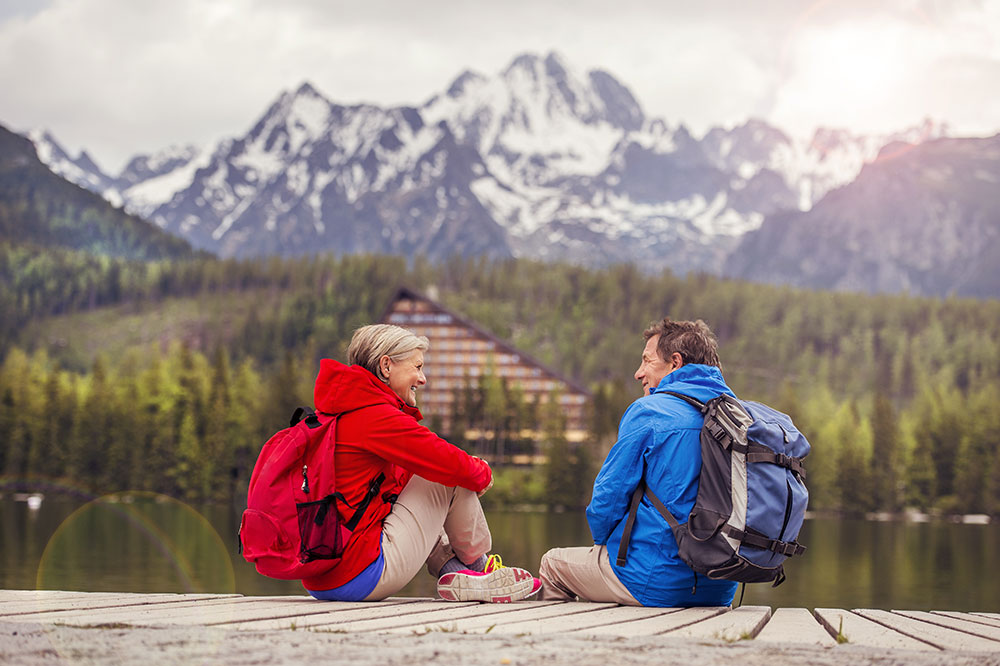 A couple in hiking gear sitting on a dock with a lake, trees, and mountains in the background